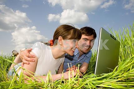 Повседневная счастливая пара на портативный компьютер на открытом воздухе. Положите на Gree