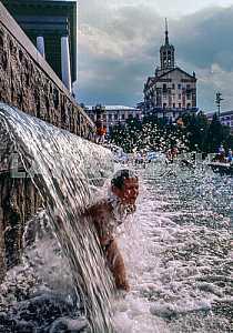 Мальчик купается в фонтане на площади Независимости в Киеве