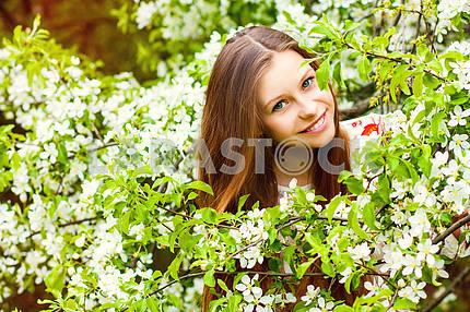 Портрет девушки красивые весной в дерево цветов.