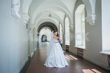 Невеста, стоя в зале, в длинном свадебном платье, с фатой и голубой лентой на ее талии, день свадьбы