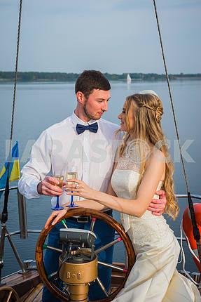 Счастливый жених и невеста, обниматься на парусной яхте с шампанским в их руках в Солнечный день; Стильное, длинное платье, галстук-бабочка
