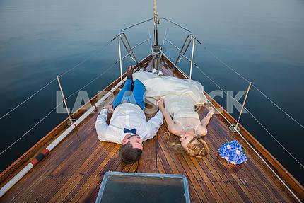 Счастливый медовый месяц парусный спорт - стильный молодой невесты и жениха, на деревянной доске парусной яхты, глядя друг на друга