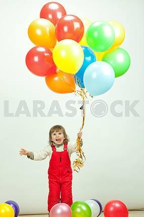 Маленькая девочка в красном прыжки с воздушными шарами