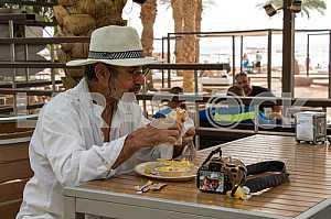 Мужчина в шляпе кушает в кафе в Эйлате