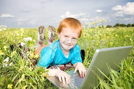 Улыбка ребенка с ноутбуком на лугу