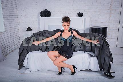 Брюнетка женщина - черный ангел с большими крыльями, красные губы, черный короткий костюм, в белой комнате