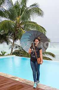 Девушка стоит с зонтом в руках на фоне океана