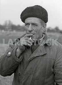 Мужчина самосел курит самокрутку