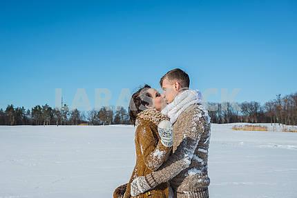 Молодая пара, поцелуи на снегу поле в Солнечный зимний день. Свадьба в деревенском стиле. Милая девушка в коротком свадебном белом платье, голубое небо на заднем плане. Браун свадебный стиль