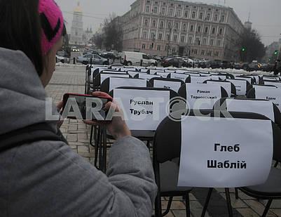 Девушка фотографирует пустые стулья с именами заключенных и пленных