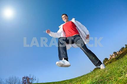 Счастливый молодой человек - прыжки конец летит в синем небе