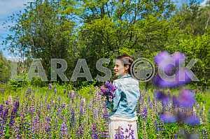 Молодая женщина, брюнетка, счастливым, стоя среди поля фиолетовыми люпина, улыбаясь, фиолетовые цветы. Голубое небо на заднем плане. Лето, солнечный день! повернулась к нему спиной.