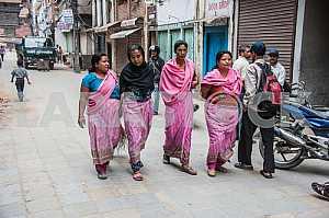 Женщины в розовых сари идут по улице Катманду.