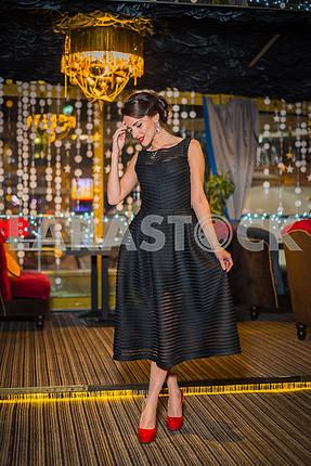 Красивая брюнетка женщина, идущая в ресторане, в черном платье и красные туфли. Улыбка с ее красными губами, застенчивый, как маленькая девочка