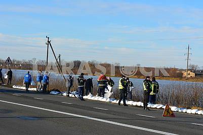 Спасатели укладывают мешки на дороге