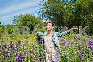 Молодая женщина, брюнетка, счастливым, стоя среди поля фиолетовыми люпина, улыбаясь, фиолетовые цветы. Голубое небо на заднем плане. Лето, солнечный день!