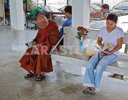 Люди читают книги на остановке