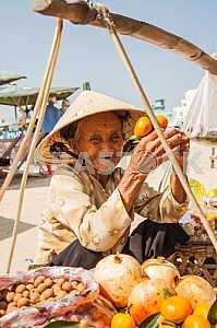 Бабушка, продавщица фруктов сидит около корзин