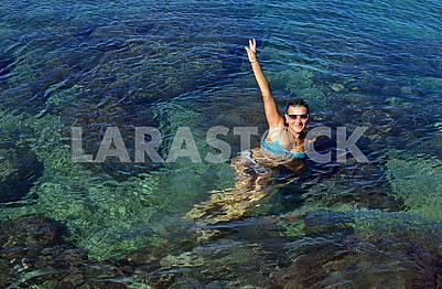 Молода жінка в купальнику плаває в морській воді