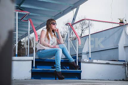 Девушка со светлыми волосами, сидя на лестнице, весна, солнечный теплый день, в солнцезащитных очках и голубых джинсах. Отдыхает, смотрит с одной стороны