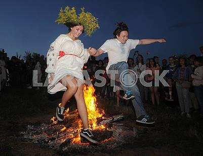 Молодые люди прыгают через костер