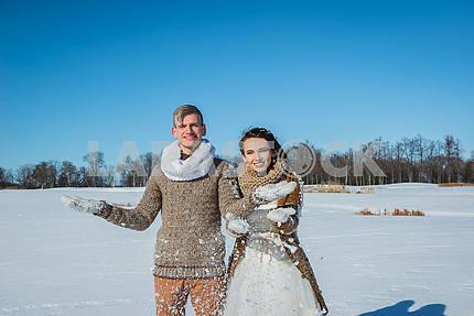 Молодая пара свадьба, играя в снегу в Солнечный зимний день. Свадьба в деревенском стиле. Милая девушка в коротком свадебном белом платье, голубое небо на заднем плане. Браун свадебный стиль