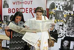 Девушки читают газеты на Форуме издателей