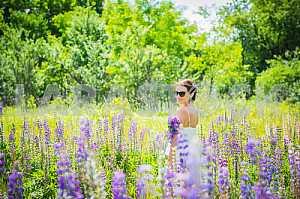 Молодая женщина, счастливый, стоя среди поля фиолетовыми люпина, улыбаясь, фиолетовые цветы. Голубое небо на заднем плане. Лето, Солнечный день, настраивая назад с букетом