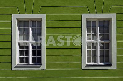 Частина фасаду старої споруди з двома вікнами на зеленій стіні
