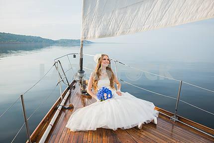 Красивая блондинка невеста в длинном белом платье позирует на парусной яхте в море с голубой букет в руке и deaming в Солнечный день