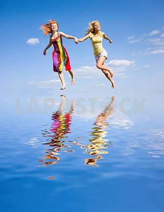 Два счастливых девушек , бежавшие на воде под голубым небом .