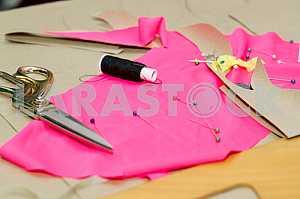 Ножницы, катушка ниток, измерительные ленты и натуральная ткань. Швейный текстиль или ткань. Рабочий стол портного. Текстильные инструменты. Копирование пространства. Вид сверху