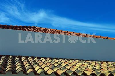 Старий і новий дахи з глиняної черепиці на тлі синього неба