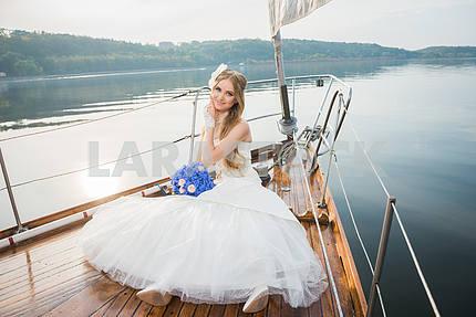 Красивая блондинка невеста в длинном белом платье позирует на парусной яхте в море с синим букетом в руке, а другая рука держится в солнечный день