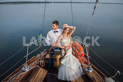 Молодожены стоят на белой яхте, на улице. Руль яхты. Свадьба на парусной яхте