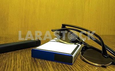 Пачка сигарет с зажигалкой и солнцезащитные очки лежат на столе