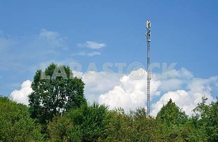Антенна мобильный телефонной связи на фоне голубого неба и облаков.