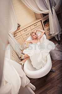 Блондинка невеста в свадебном платье, лежа в ванне, мечтая о жениха
