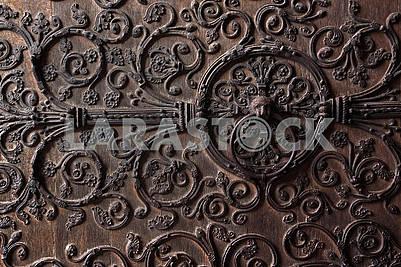 Старая деревянная дверь с металлическим орнаментом