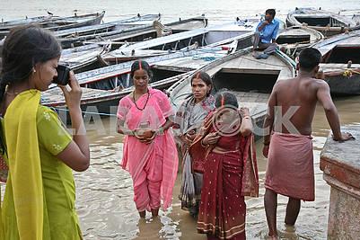 Женщины фотографируются после омываются в водах священной реки Ганг