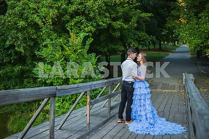 Пара любви, влюбленная, вместе в лесном парке, на деревянном мосту, девушка в красивом фиолетовом платье, солнечный вечер, лето