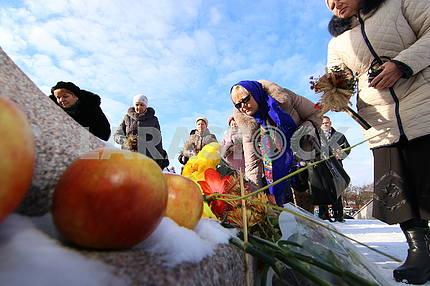 Люди возлагают цветы к мемориал жертвам политических репрессий
