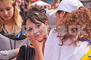 Девушка рисует на лице герб Украины