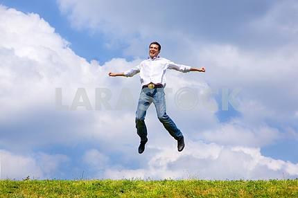 Счастливый человек прыгает на поле