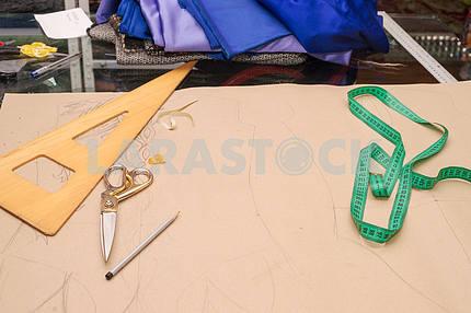 Инструменты для кожанного ремесла на деревянном фоне. Рабочий стол мастера по коже. Кусок шкуры и рабочие инструменты ручной работы на рабочем столе
