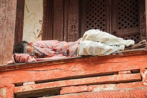 Мужчина спит на балконе старого храма.