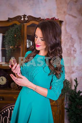 Красивая брюнетка женщина с настоящим в ее руках, в том числе новогодние украшения в ярко-синем платье, улыбаясь