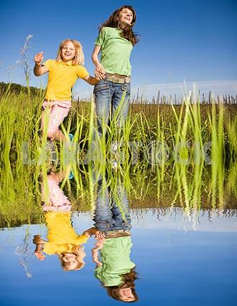 Счастливый женщина и девочка, делая упражнения на поле