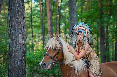 Красивая девушка в костюме американского индейца, верхом на лошади в форресте