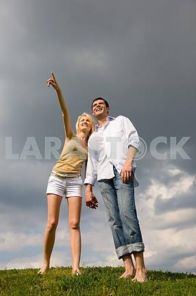 Счастливый молодая пара, глядя на что-то над зеленый луг . Массачусетс